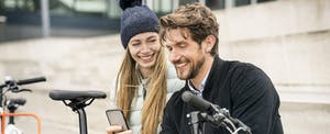 Couple sitting together on outside steps with a bike, looking at a phone and smiling