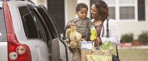 Mother holding toddler son and unloading groceries from car