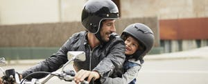 Man sitting on a motorcycle, with his child behind him
