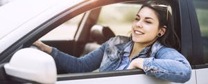 Smiling young woman driving car with window down
