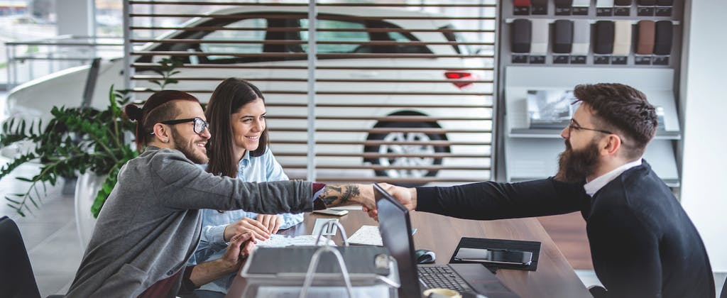 Young couple at car dealership discussing dealer fees with sales person