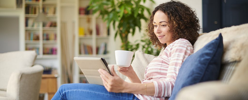 Young woman sitting on her sofa, drinking coffee and looking at her tablet