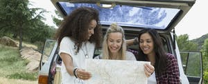 Three women sitting on the back of a truck, looking at a map