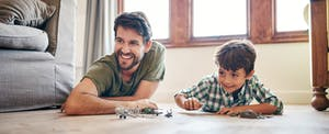 Young boy and his father playing with toy cars at home