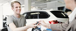 Man smiling at a car dealership, somebody is handing over car keys to him