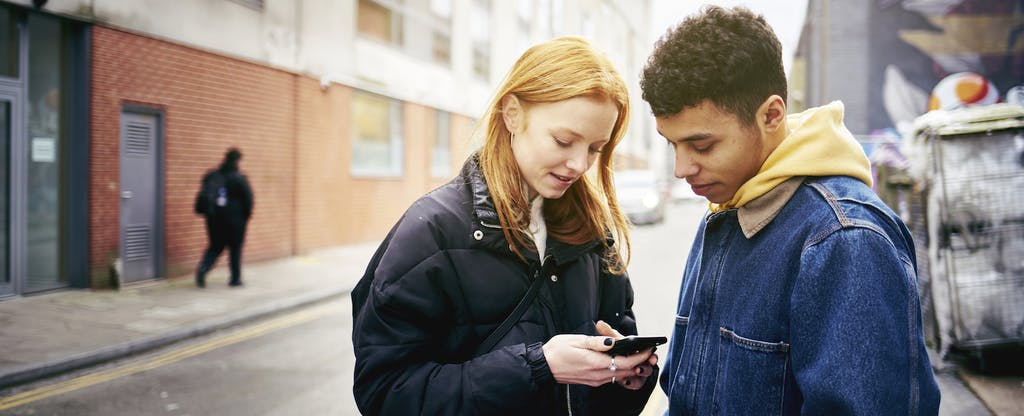 Two teenagers standing together in the street, looking at a phone