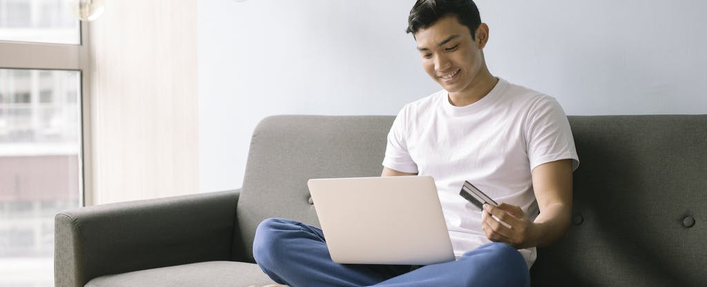 Young man sitting on couch and holding credit card to learn about a finance charge