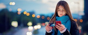 Woman standing outside at night, looking at her phone and credit card