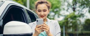 Young woman looking at cell phone to see how much her car is worth