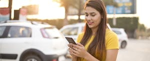 Woman on cell phone looking up a free Carfax report