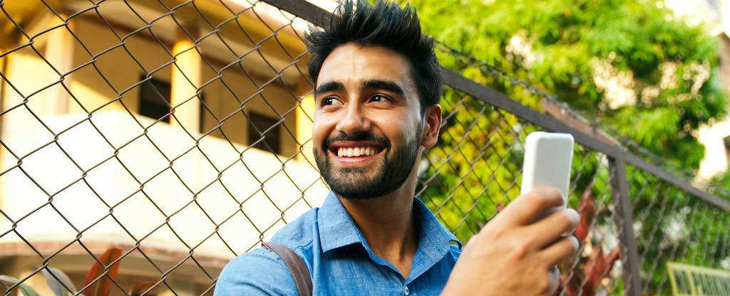 Man standing outside, holding his smart phone and smiling