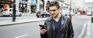 Man standing outside in the street, looking at his phone