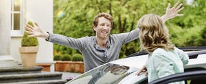 Man and woman standing next to a car. He's smiling with his arms outstretched.