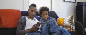 Woman sitting on couch with son, using her smartphone to research states with no income tax