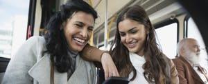 Two women sitting together on a bus, looking at a phone, confident they know what to do with a 1099-R.