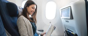 Woman on airplane reading a magazine