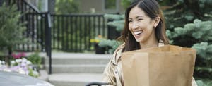 Woman standing outside, unloading groceries from her car and smiling