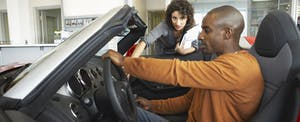 Man at car dealership deciding if he should buy a car with cash