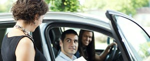 Woman standing outside of a car, holding paperwork and talking to a couple sitting in the car