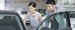 Young couple looking at new car in showroom