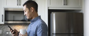 Man standing in his kitchen, holding a cup of coffee and looking at his phone