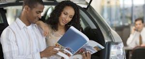 Man and woman reading brochure at car dealership