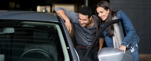 Couple looking at a car to buy at the dealership