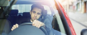 Young man driving car and worried about auto loan debt