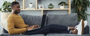 Young man sitting on couch with laptop looking up money market vs cd