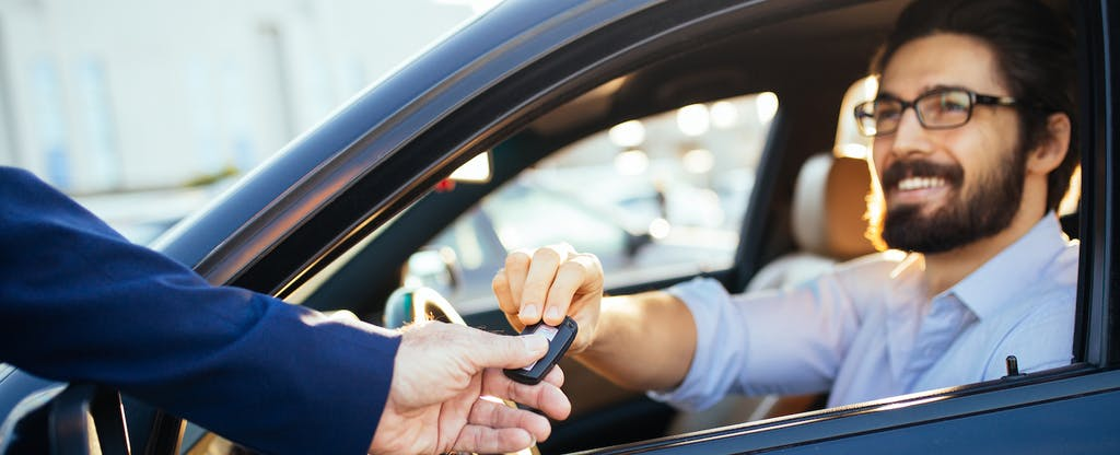 Man sitting in a car, accepting a key from an off-camera person's outstretched hand