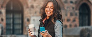Woman walking outside with a coffee in her hand, looking at her phone and smiling