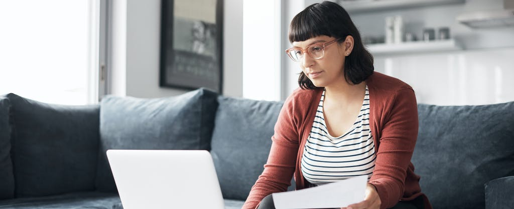 Woman using her laptop while going through some paperwork