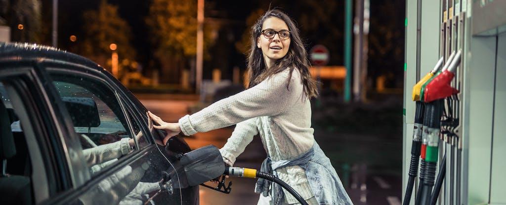 Woman pumping gas at night