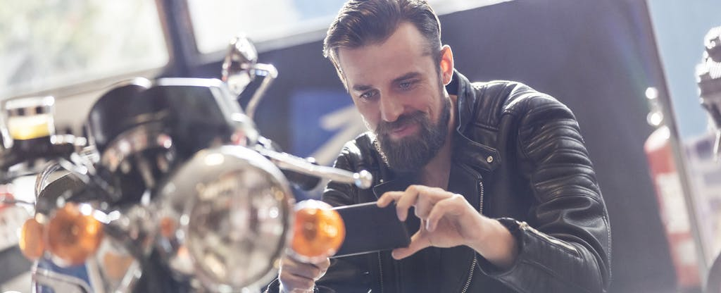 Man with camera phone photographing motorcycle in shop