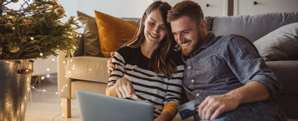 Young couple celebrating Christmas at home. They are sitting on floor and shopping online.
