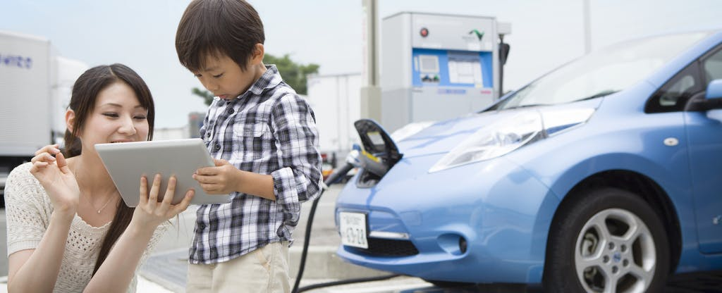 Mom and child using tablet while charging electric car