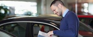 Young man reading brochure at car dealership