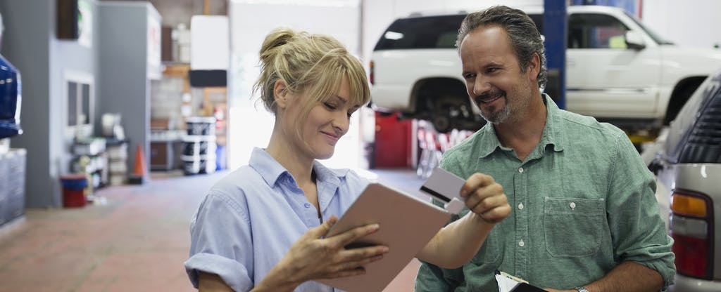 Female mechanic talking with a customer