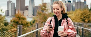 Woman walking in New York, texting on smartphone with one hand and holding a coffee with the other