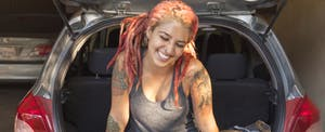 Young woman with pink dreadlocks sitting in trunk of car