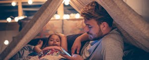 Man sitting in a homemade tent with his young daughter, reading on his phone