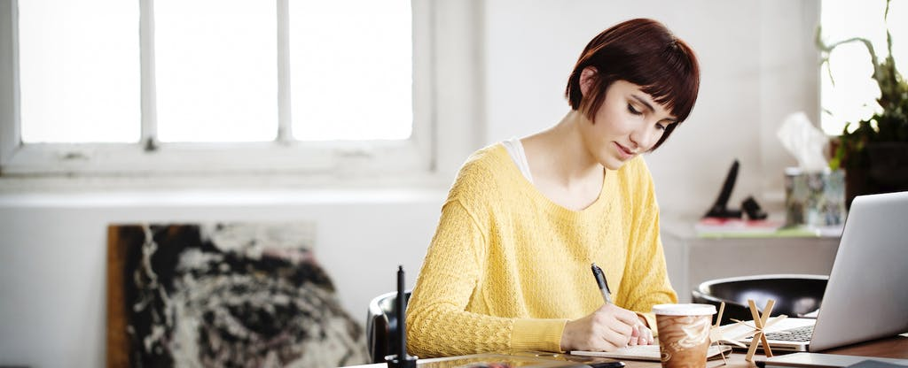 Woman sitting at her desk with her laptop open, writing in a notebook