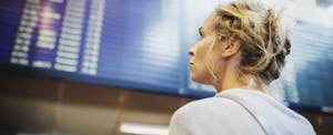 Businesswoman looking at arrival departure board in airport