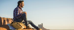Man taking a break from a hike, sitting on an outcrop and looking over the desert landscape