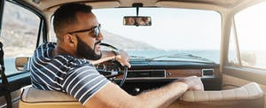 Young smiling man wearing sunglasses driving a car