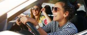 Laughing young girlfriends in sunglasses traveling in a car