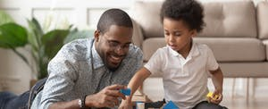 Father and toddler son playing with blocks in their living room