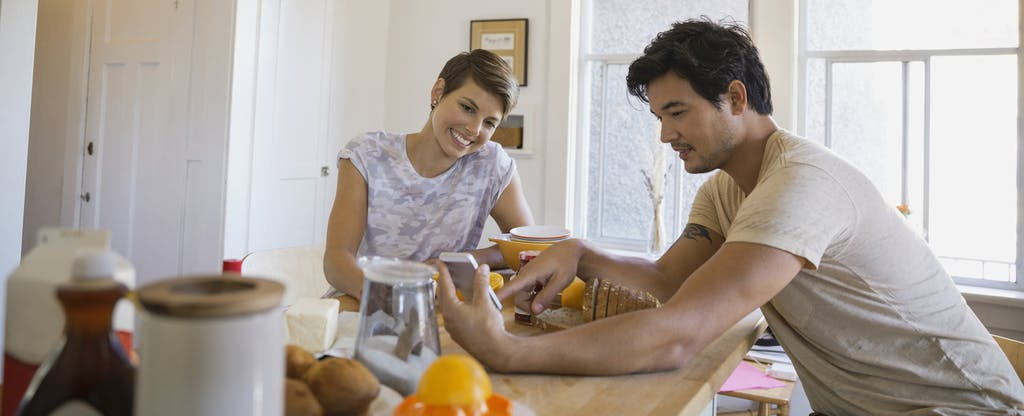 Man and woman sitting together at their kitchen table, looking at a phone together