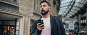 Young man walking in the city and holding phone