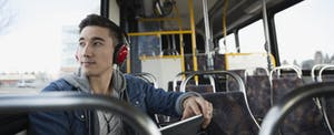 Man sitting on a bus, wearing headphones, holding a tablet and looking out the window